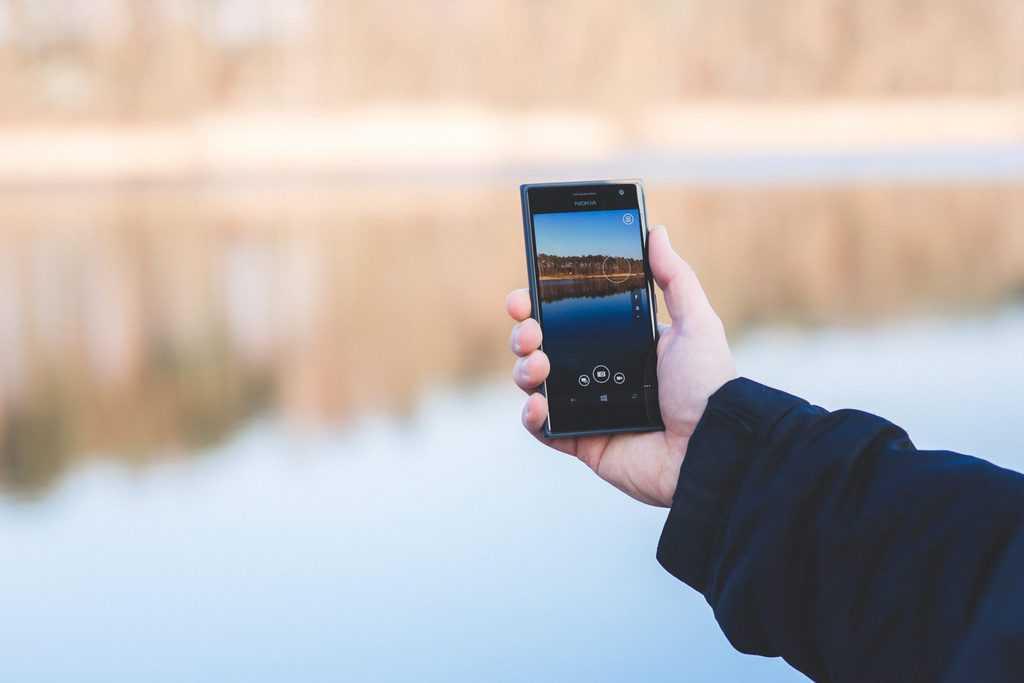 man hand smartphone lake scaled