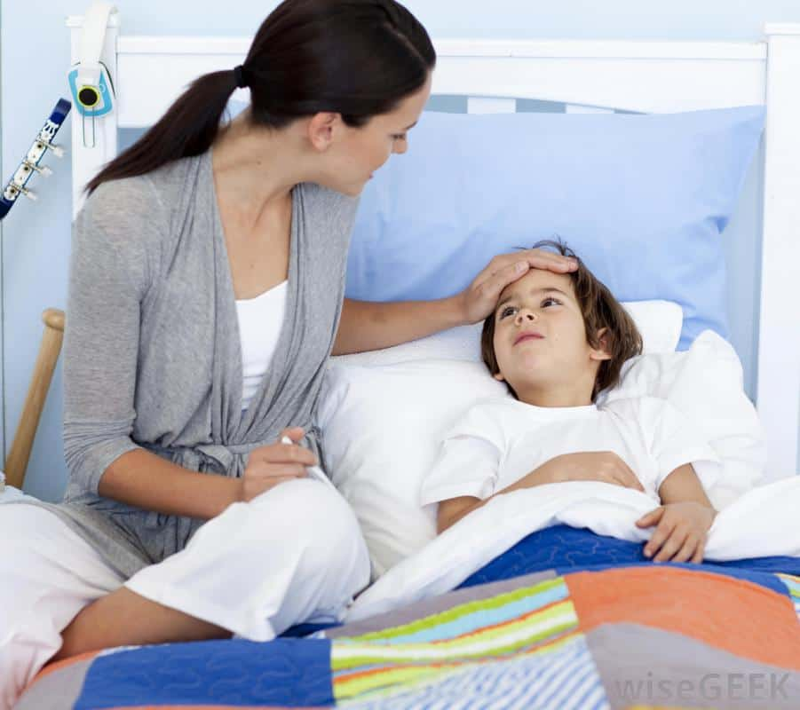woman pressing hand against forehead of sick child in bed