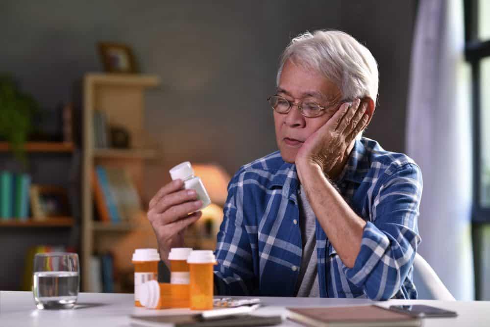 Asian older man with medicine bottles e